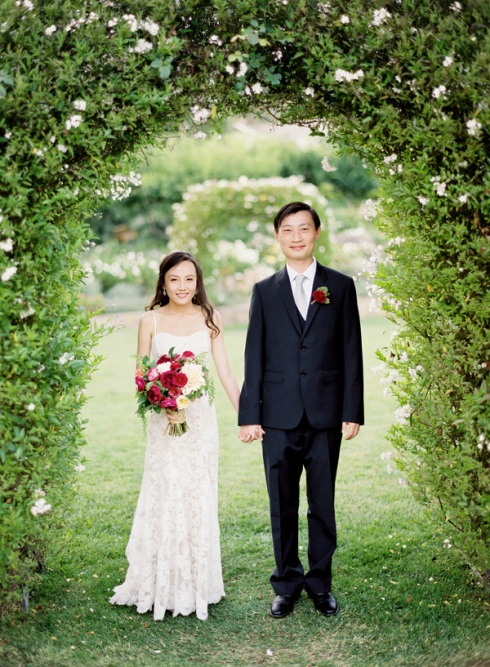 Bride and groom under garden arch