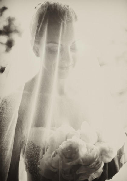 Bride behind veil in sepia